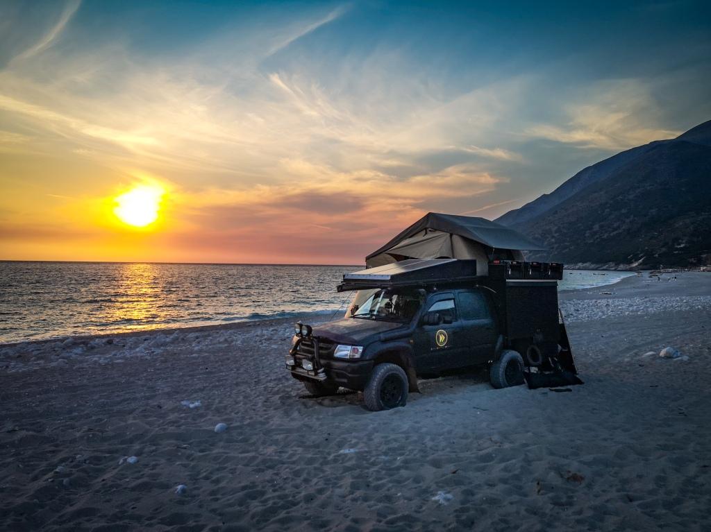 Zachód słońca, samochód terenowy na plaży w Albanii. Obozowanie, spanie  na dziko. Sunset, 4x4 truck on a beach in Albania. Wild camping, sleeping, camping on a beach in Albania.